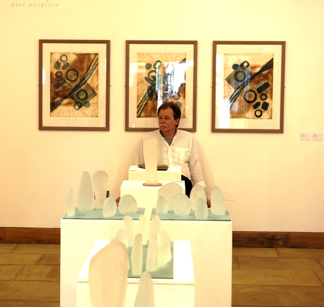 Paul Musgrove with glass sculptures in the foreground and woodblock prints behind